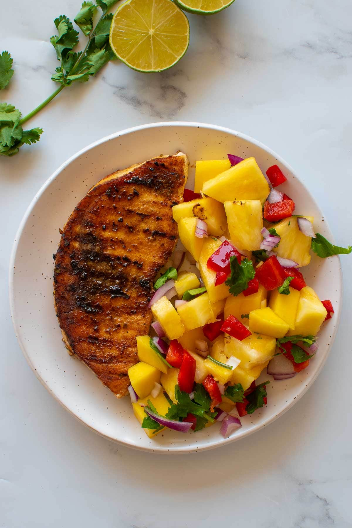 Blackened swordfish and pineapple salad on a plate.