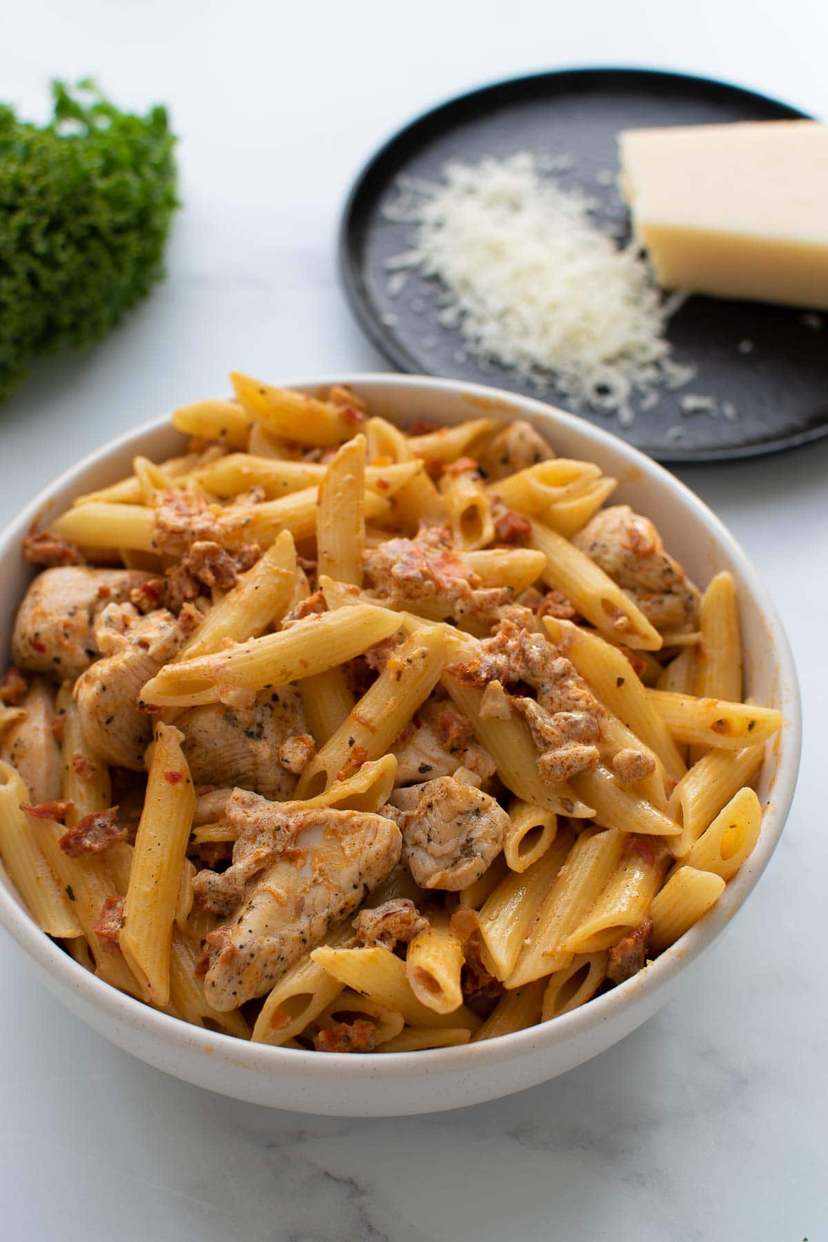 A bowl of chicken and chorizo pasta, with parmesan in the background.