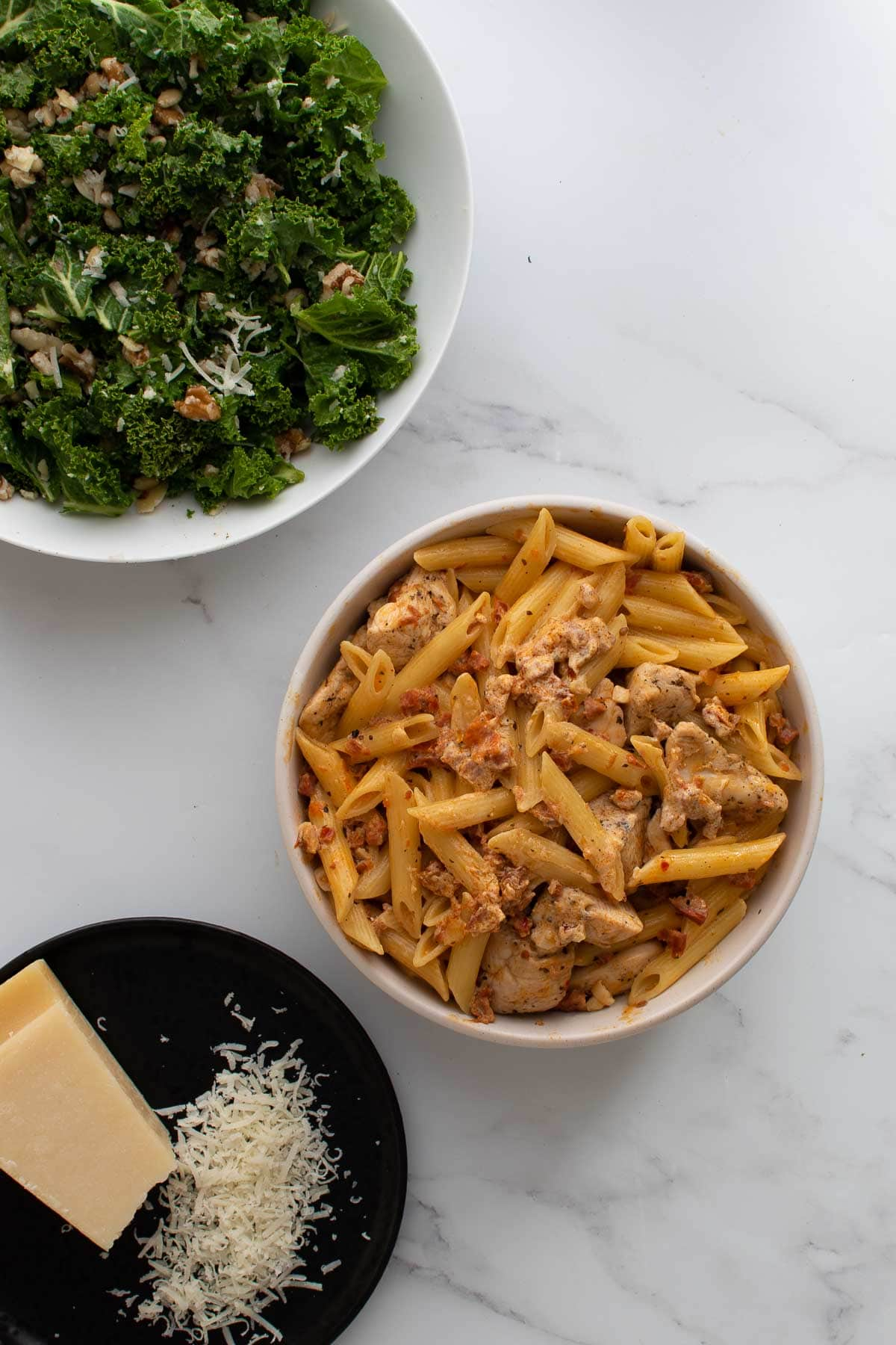 A bowl of chicken and chorizo pasta, with kale salad on the side.