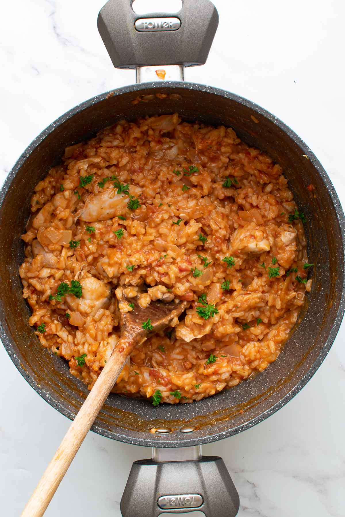 A large pot with creamy chicken chorizo risotto with Parmesan.