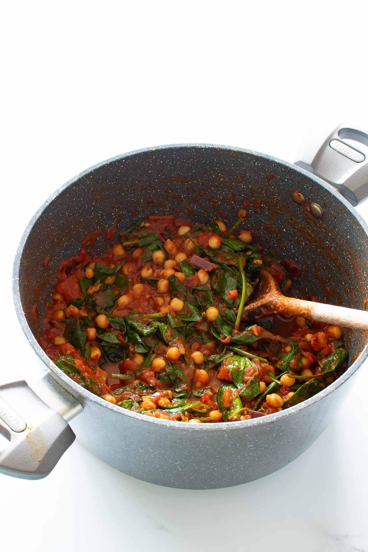 A pot of chickpea and spinach curry with tomatoes.