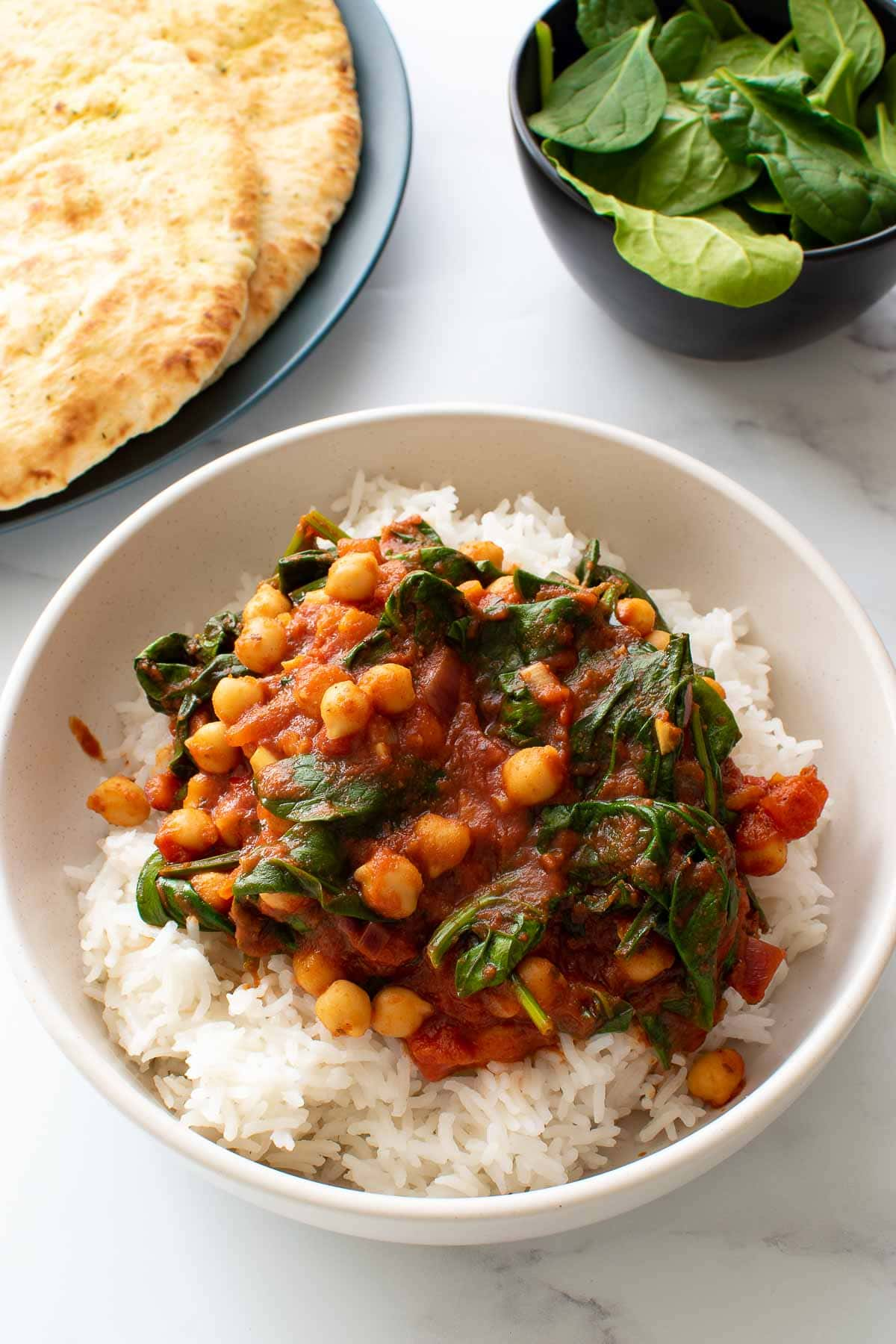 Chickpea and spinach curry in a bowl with rice.