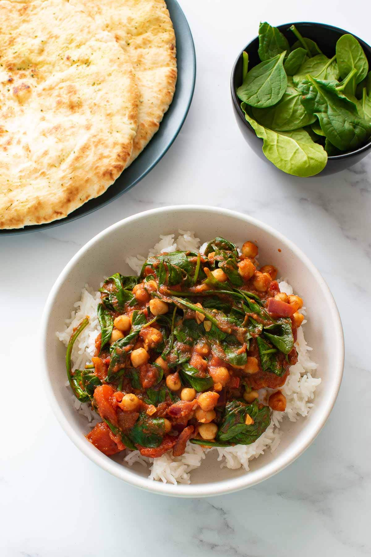 A bowl of curry with spinach and chickpeas.