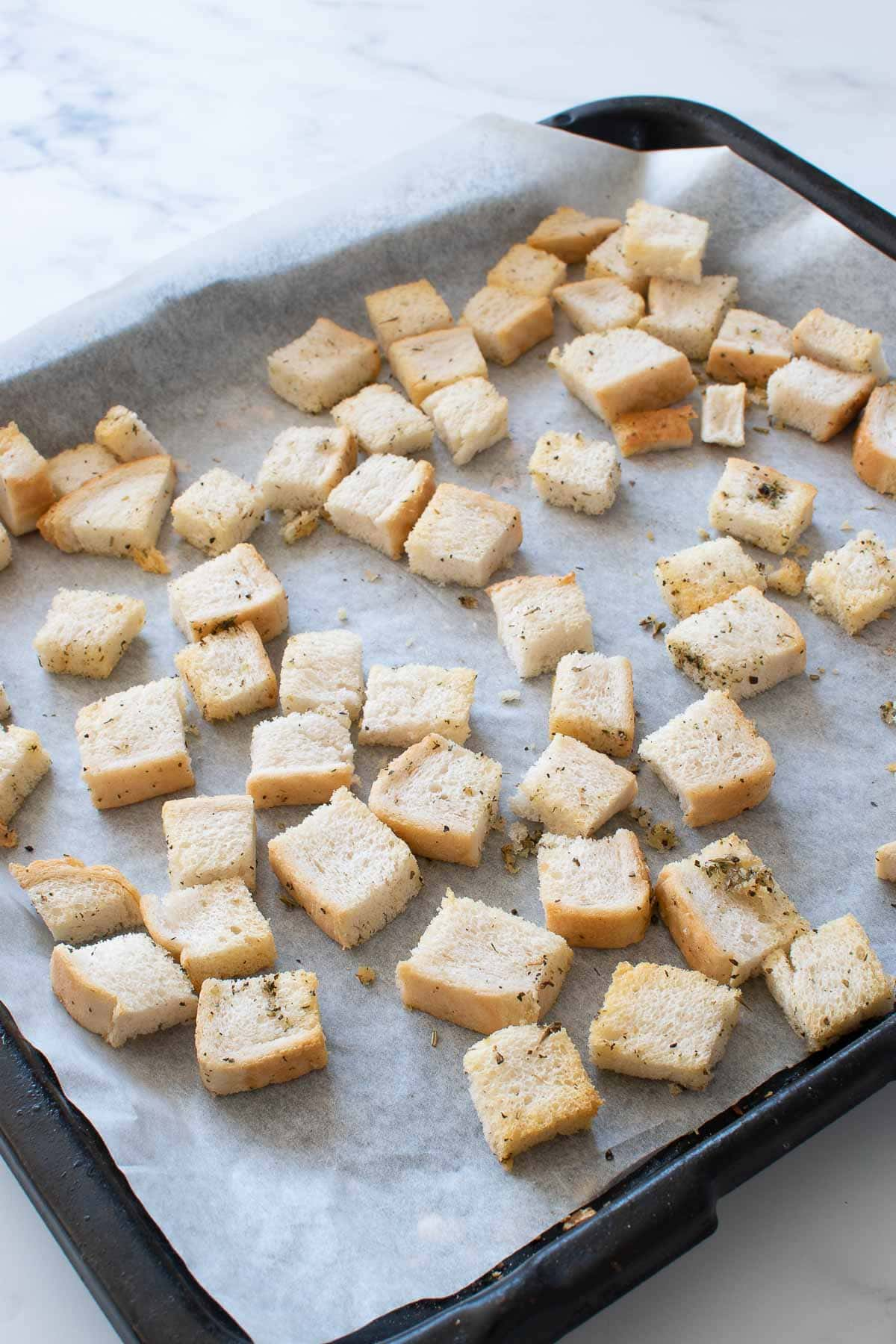 A baking sheet with homemade croutons.