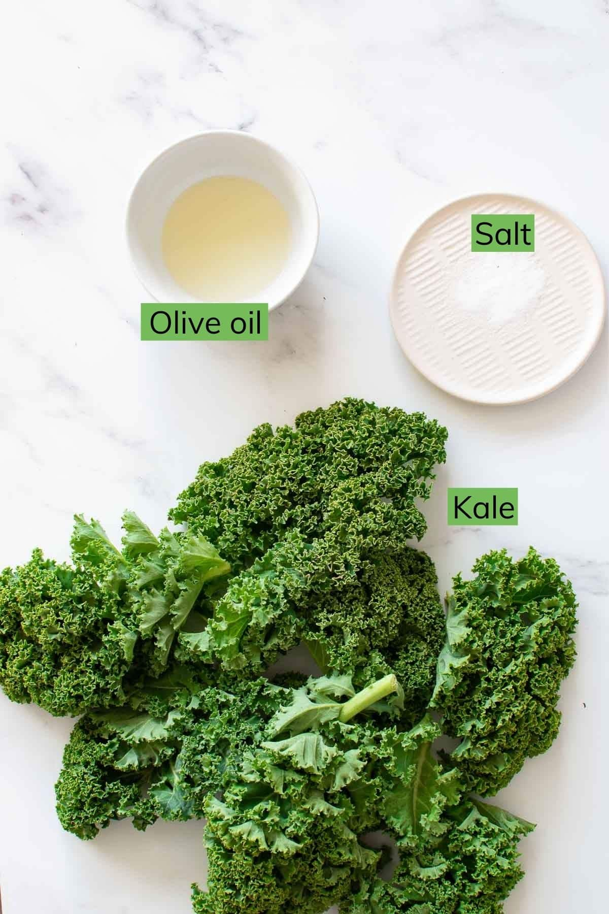 Olive oil, salt and kale on a table.