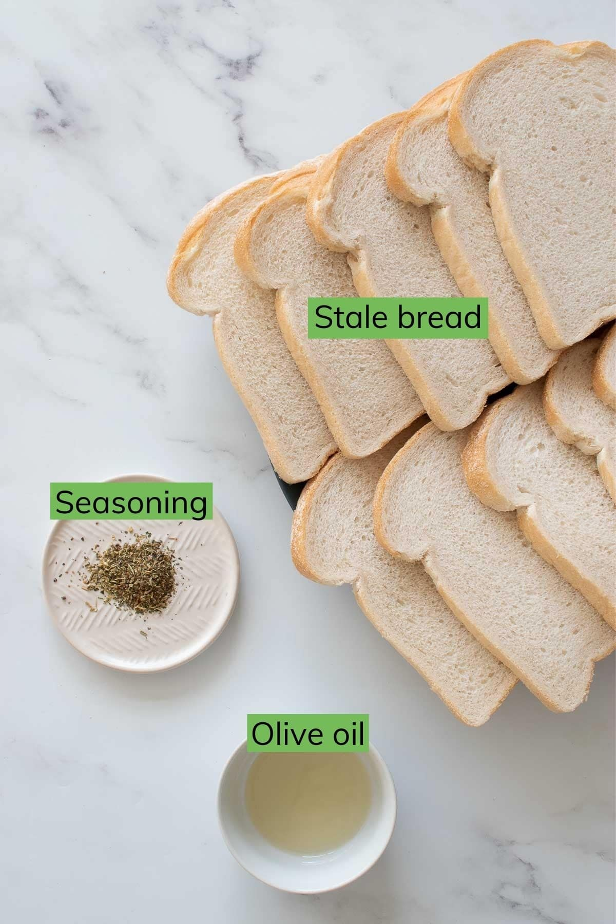 Stale bread, seasoning and olive oil on a table.