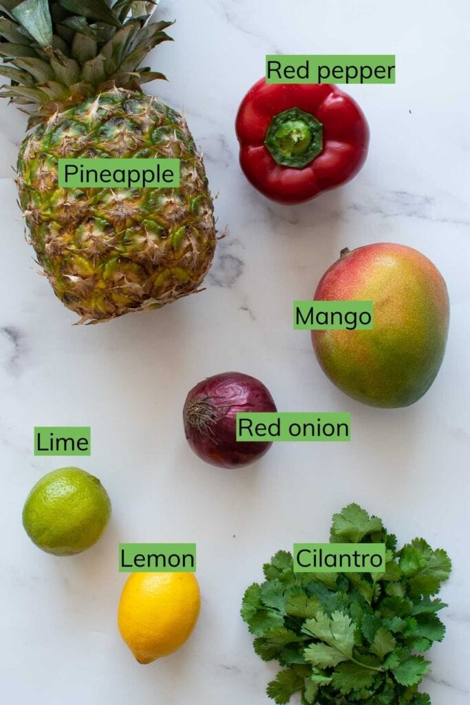 The ingredients required to make pineapple mango salsa laid out on a table.