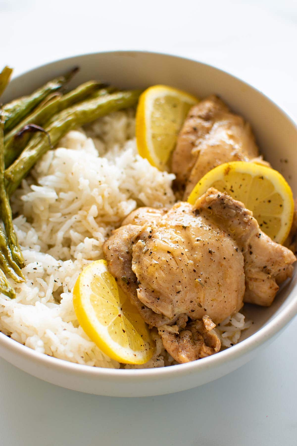 Lemon garlic chicken thighs in a bowl with rice and green beans.
