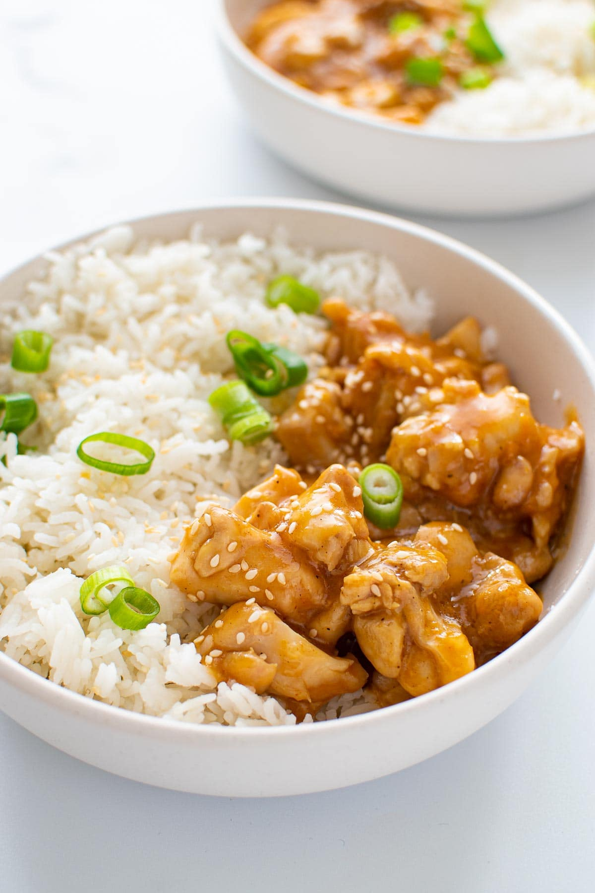 A bowl with sticky orange chicken, rice and green onions.