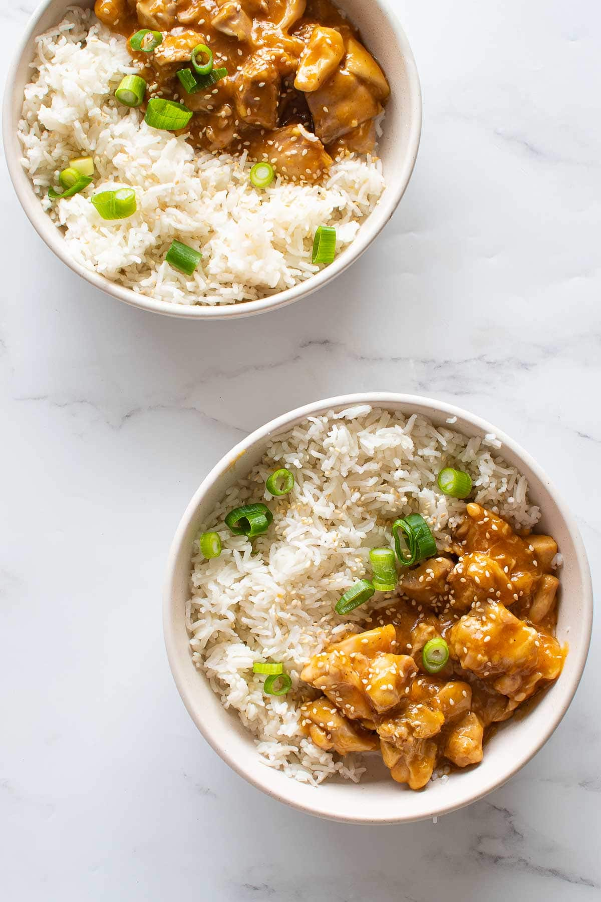 Two bowls with orange chicken and rice.