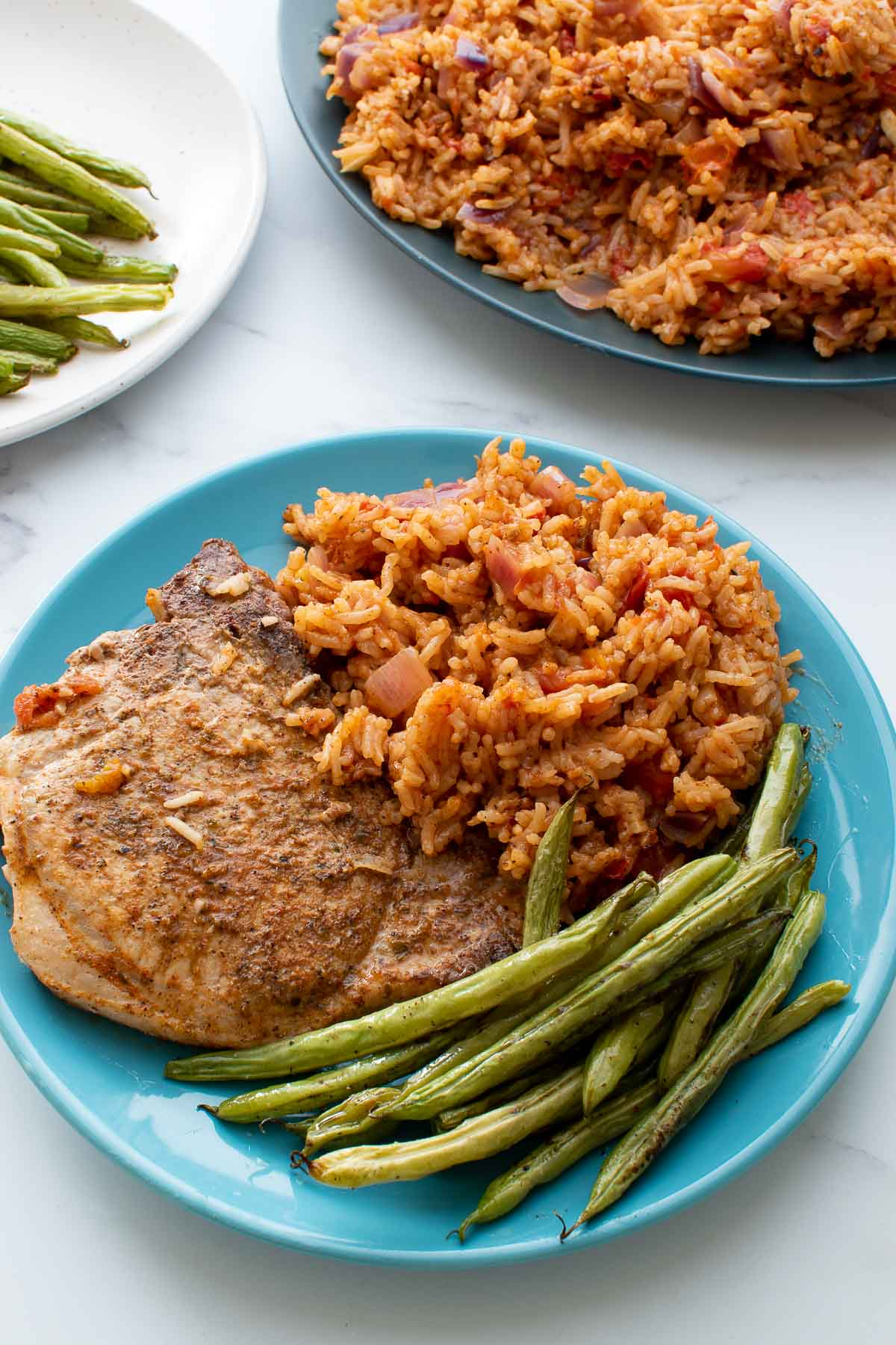 A plate with pork chop, rice and roasted green beans.