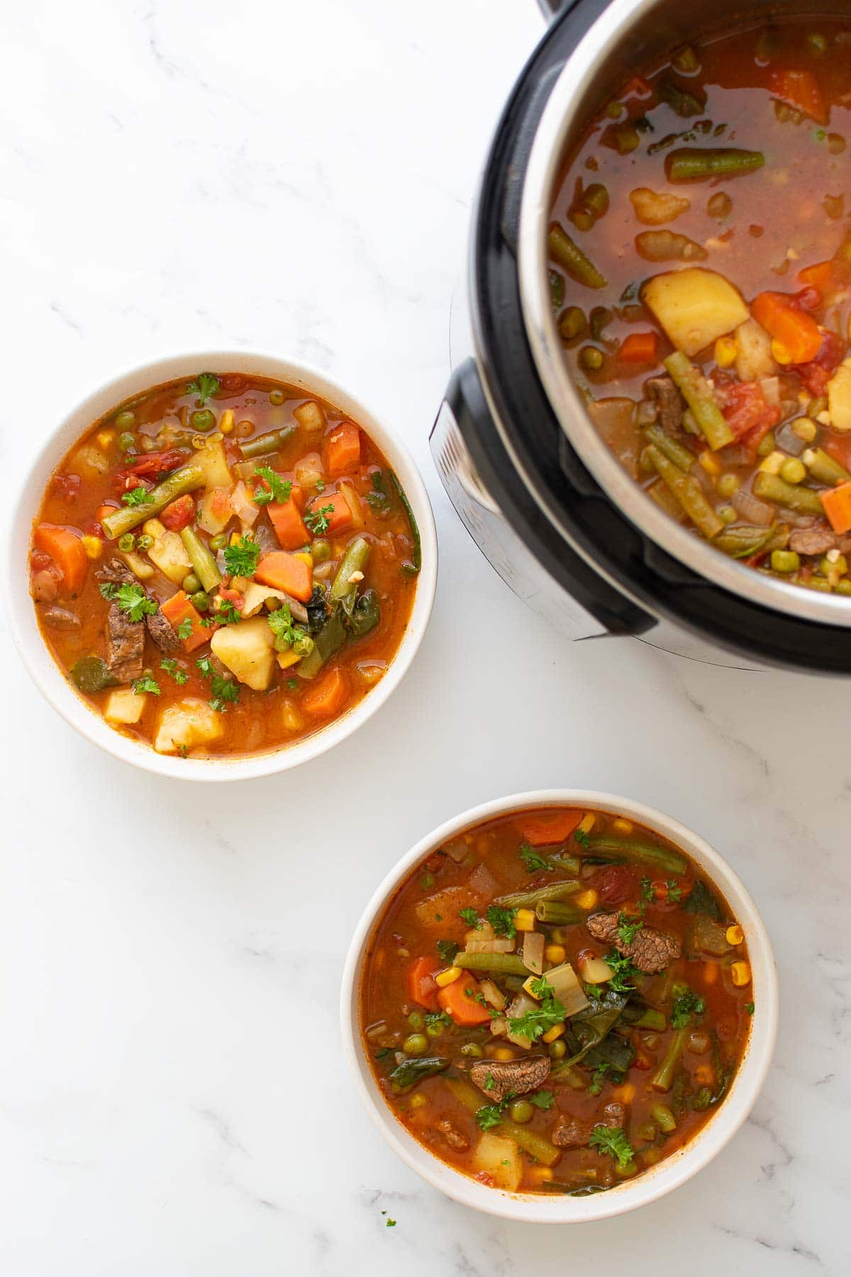 Two bowls of Instant Pot beef soup with vegetables.