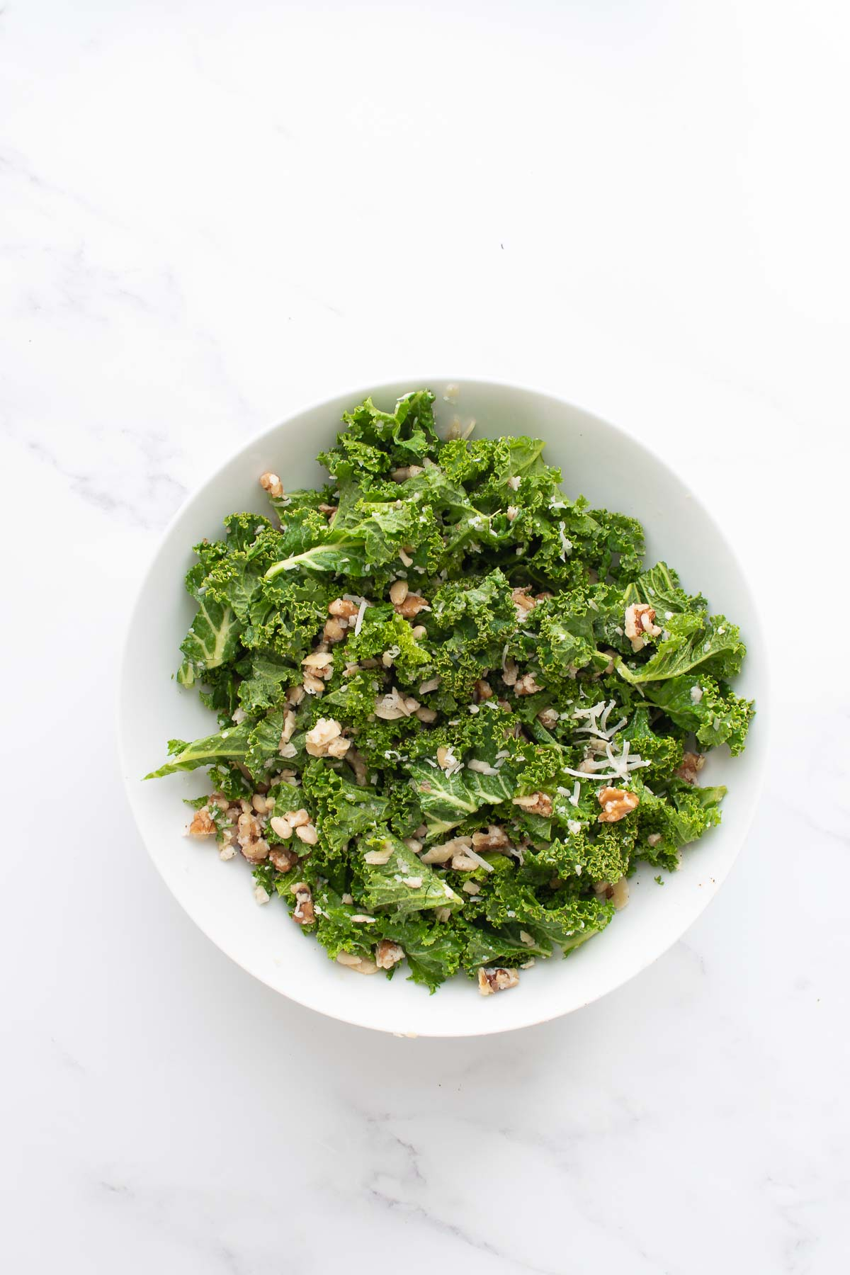 A bowl with lemon kale salad with nuts and parmesan.