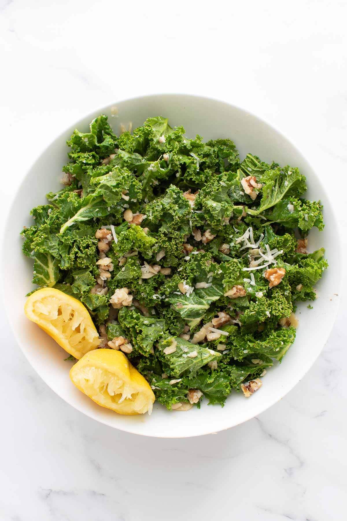 Lemon kale salad in a bowl, with lemon on the side.