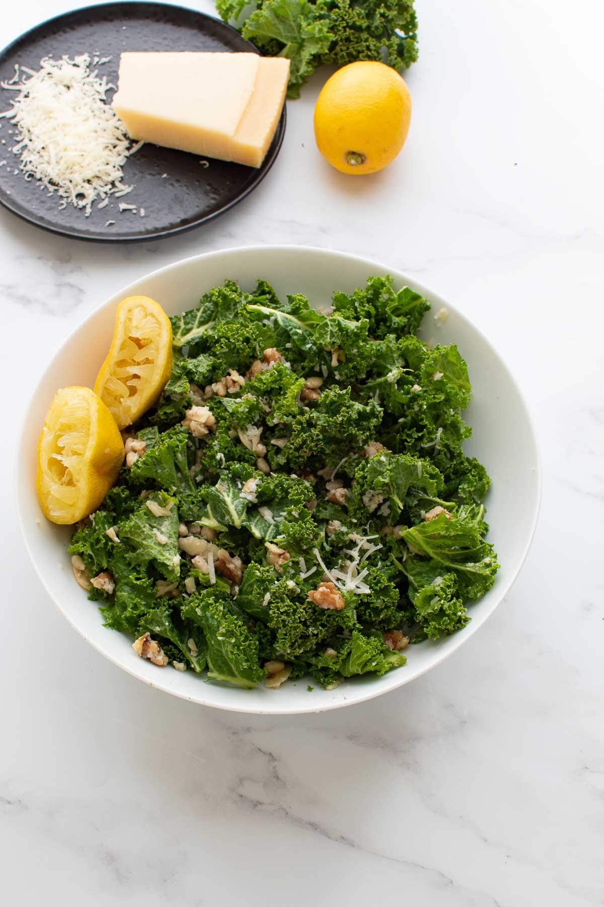 A bowl of lemon kale salad, with lemon and parmesan in the background.