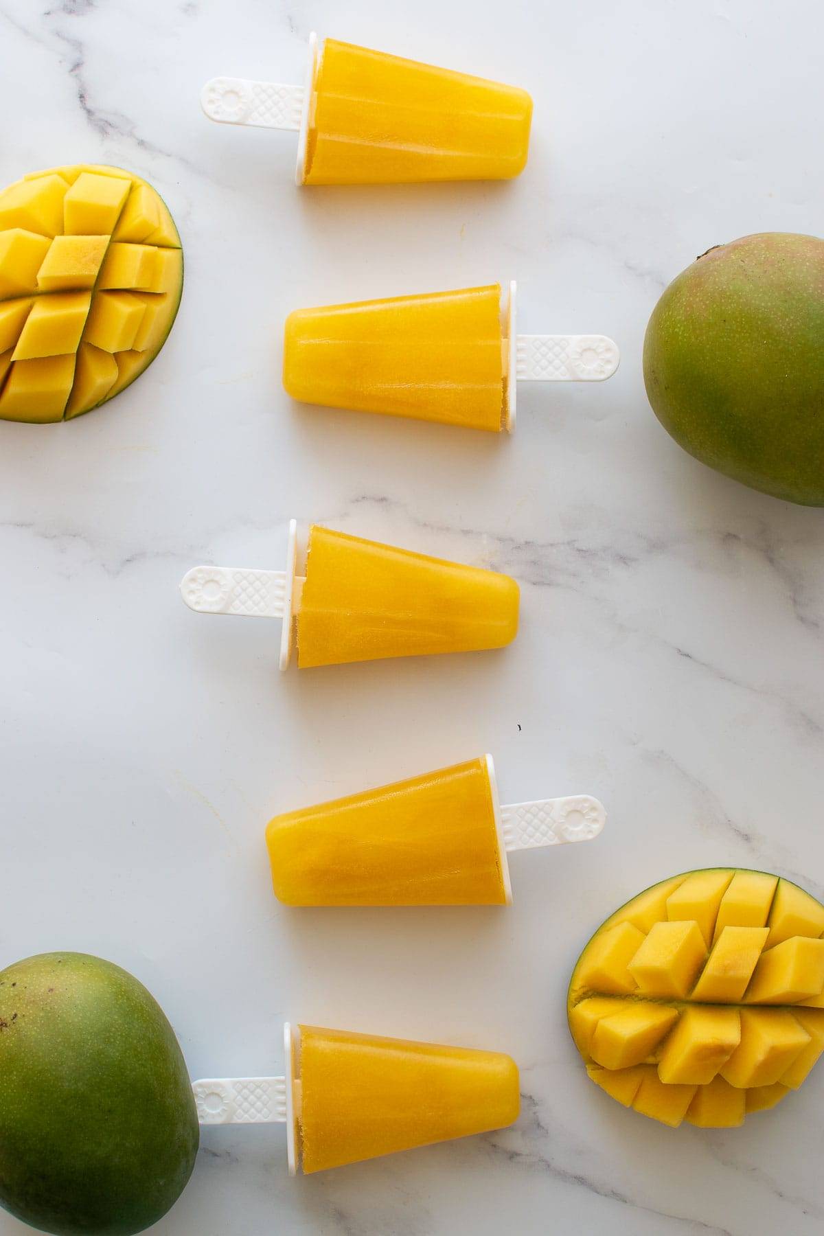 Mango popsicles lined up on a table.