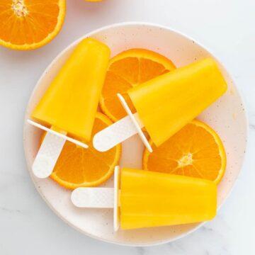 Orange popsicles laid on top of orange slices.