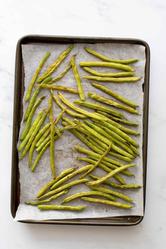Oven roasted green beans on a baking sheet.