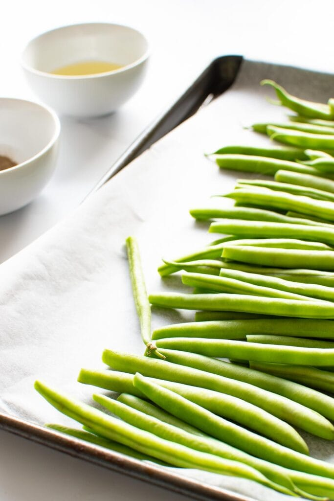 Green beans on a baking sheet, with seasoning and olive oil on the side.