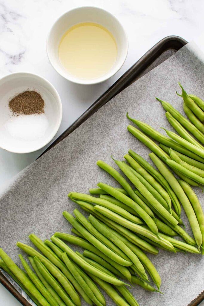 Seasoning, olive oil and green beans on a table.