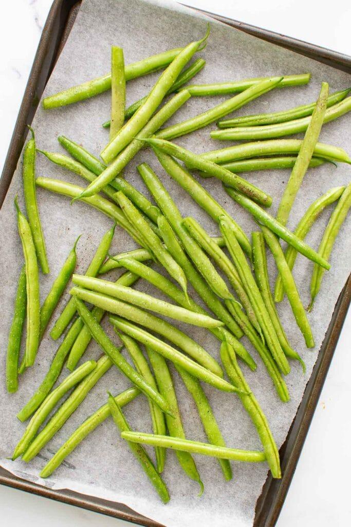 Seasoned green beans on a baking sheet.