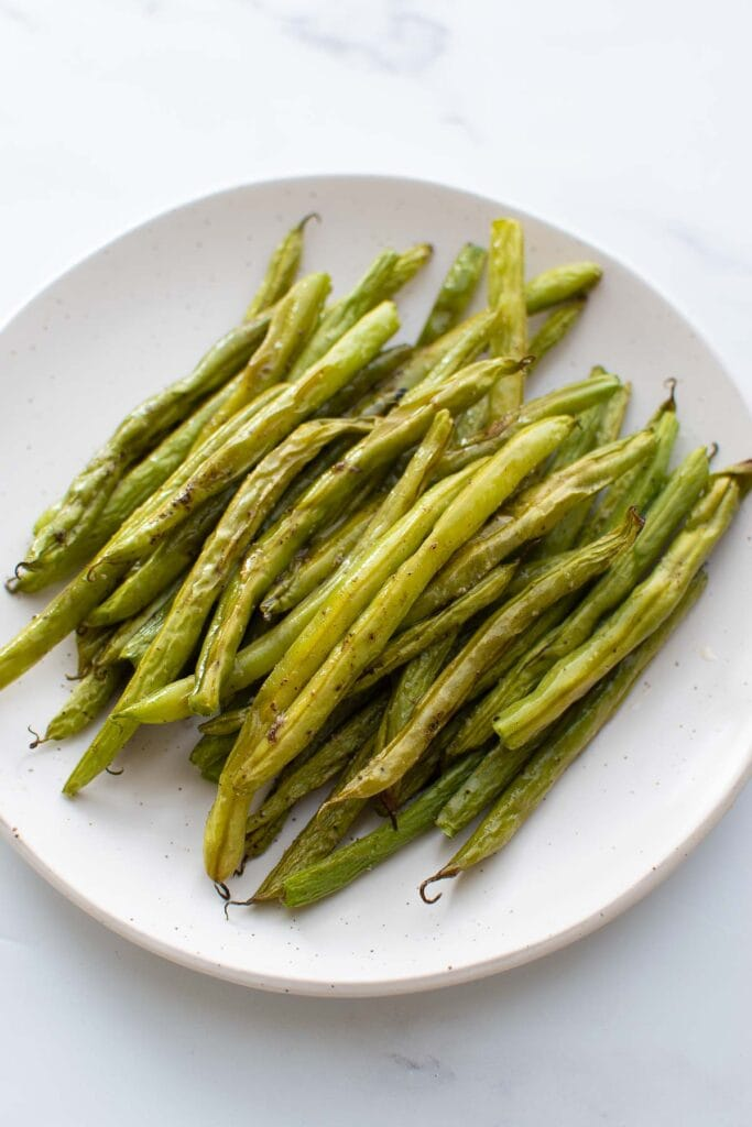 A plate with roasted green beans.