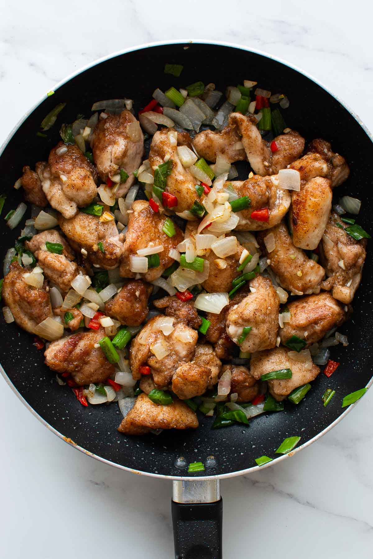 A skillet with salt and pepper chicken with chili.