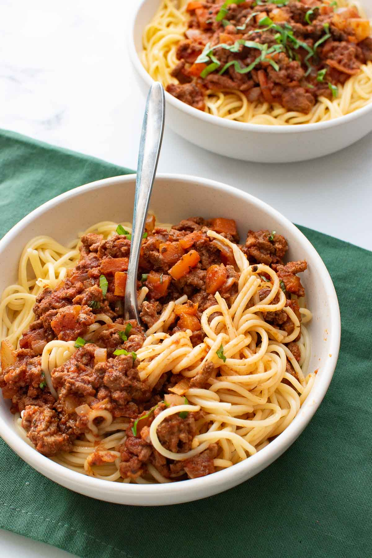 A bowl of spaghetti bolognese, with a fork.