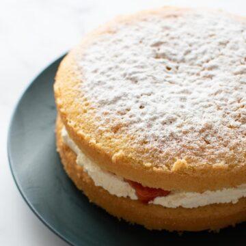 Vanilla sponge cake with whipped cream and strawberry jam.