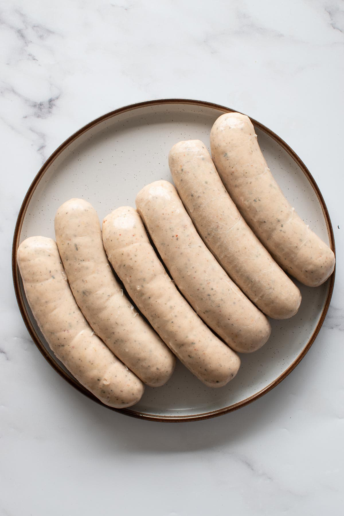 Raw bratwurst sausages on a plate.