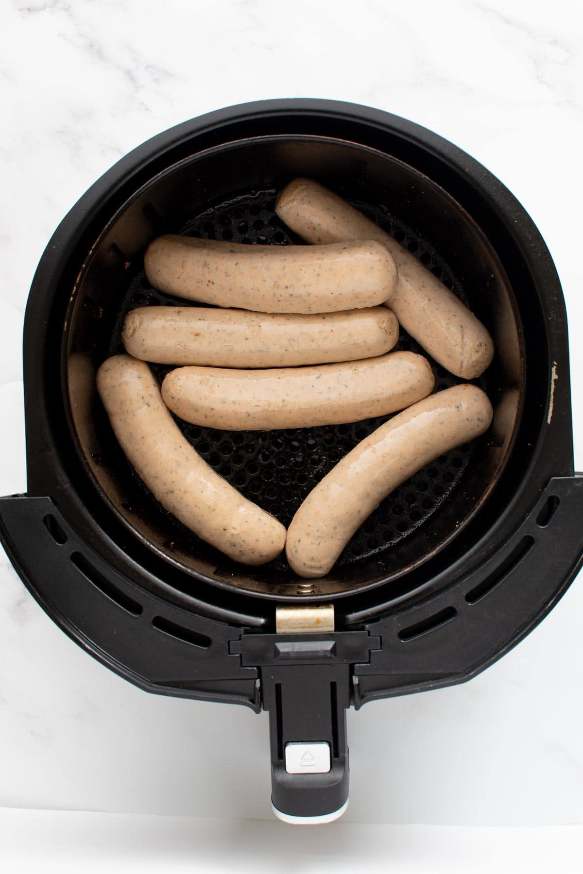 Uncooked brats in an air fryer.