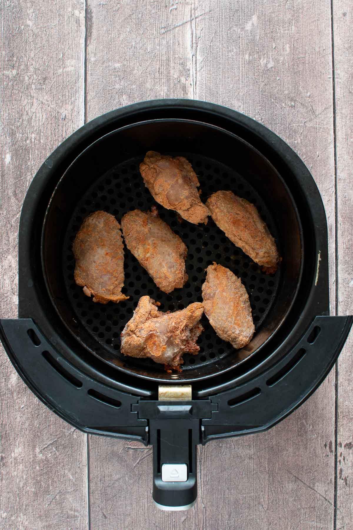 Frozen chicken wings in an air fryer.