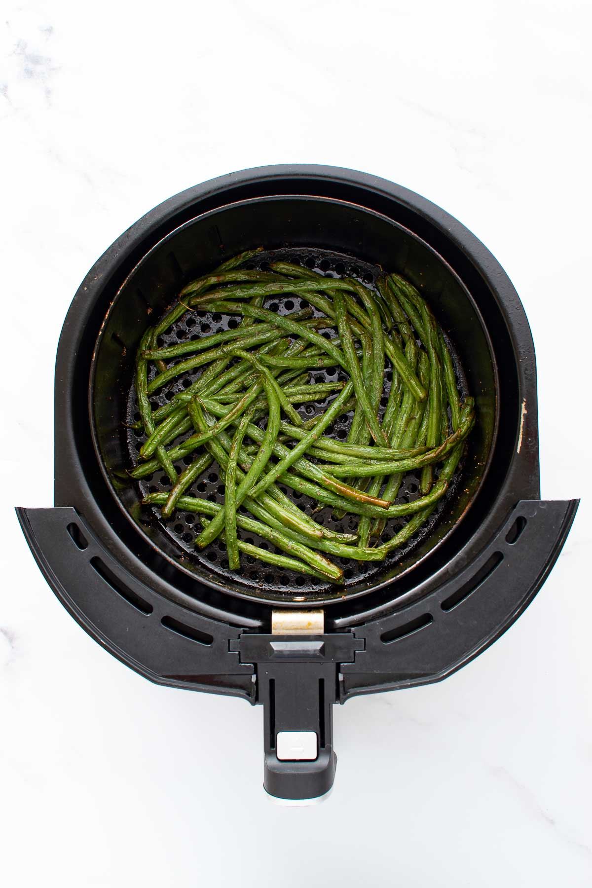 Roasted green beans in an air fryer.
