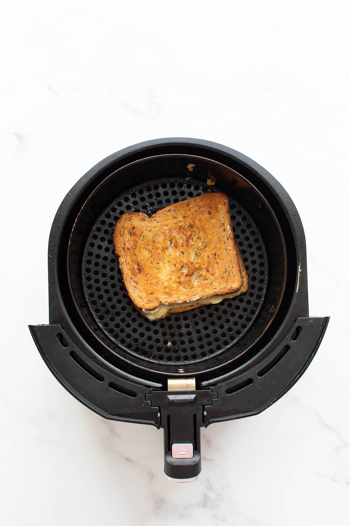 Air fryer with grilled cheese sandwich.