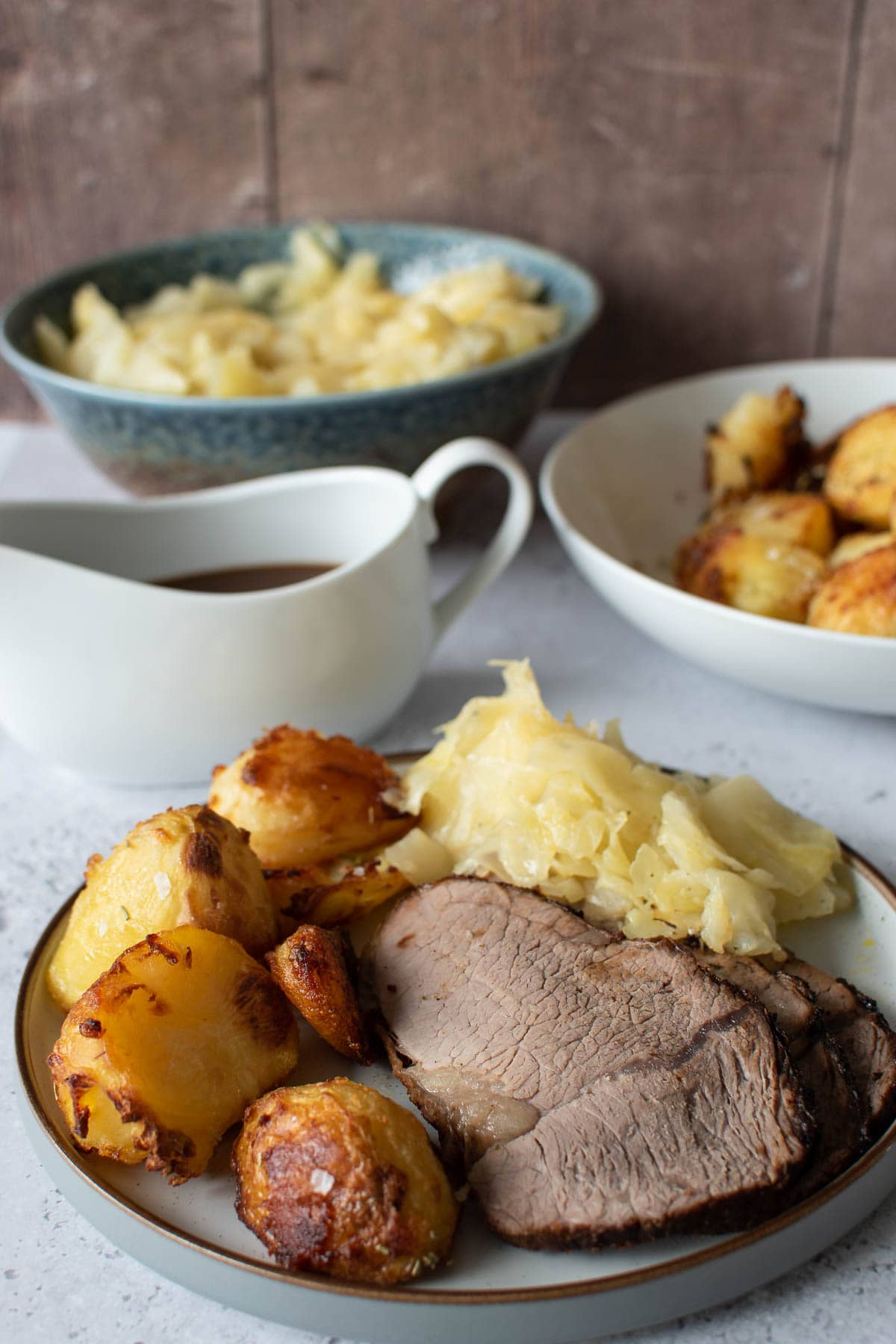 Roast dinner with air fryer roast beef, instant pot cabbage, crispy roasted potatoes and gravy.