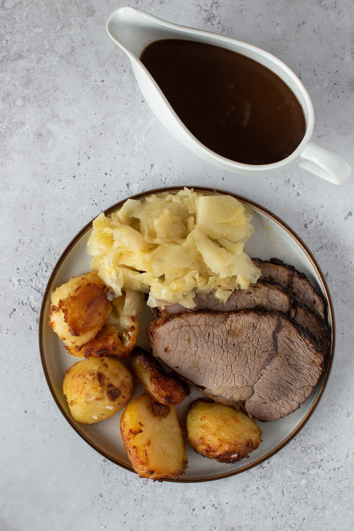 A plate with roast beef, cabbage and roasted potatoes, with gravy on the side.