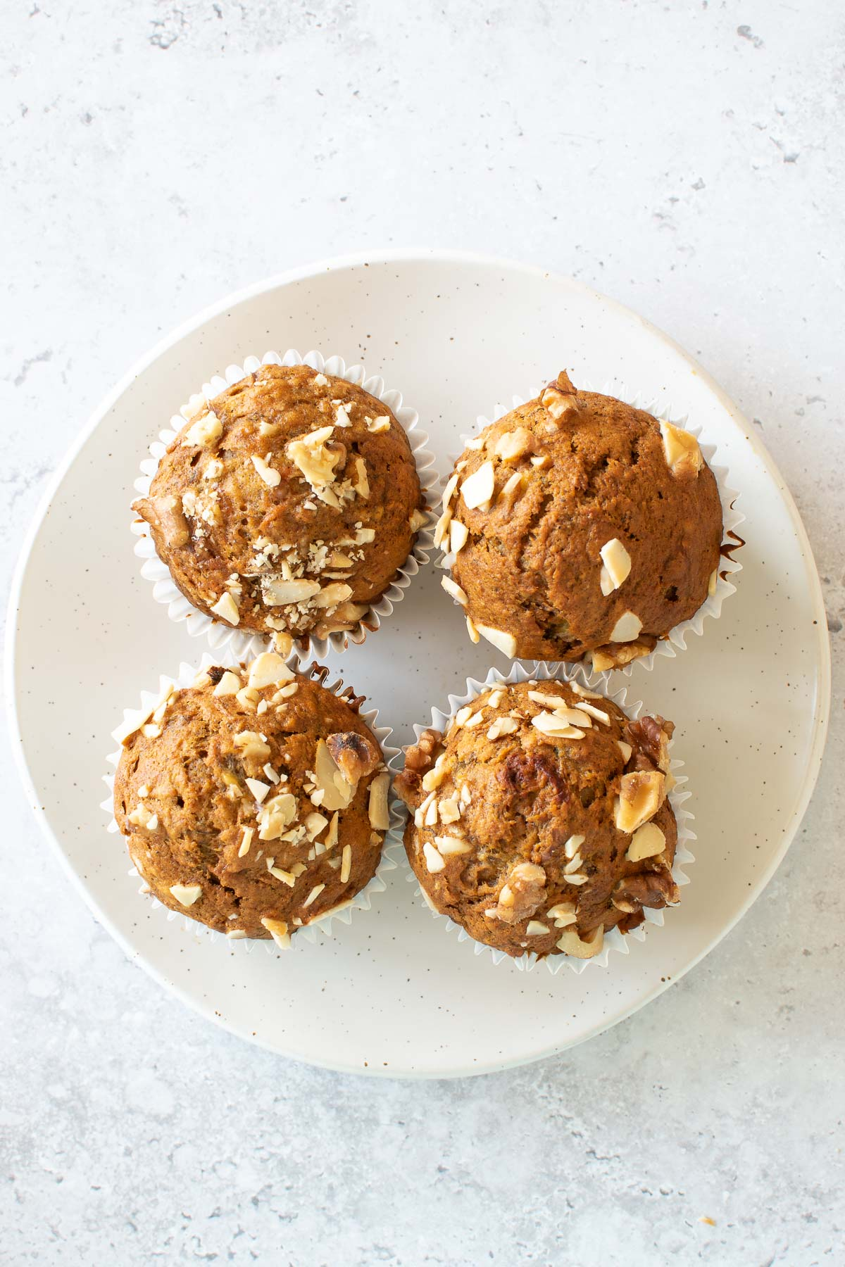 Four muffins with banana and carrots on a plate.