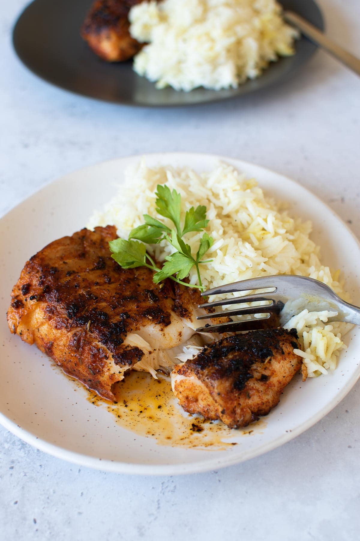 Blackened cod and rice, with a fork cutting into the fish fillet.