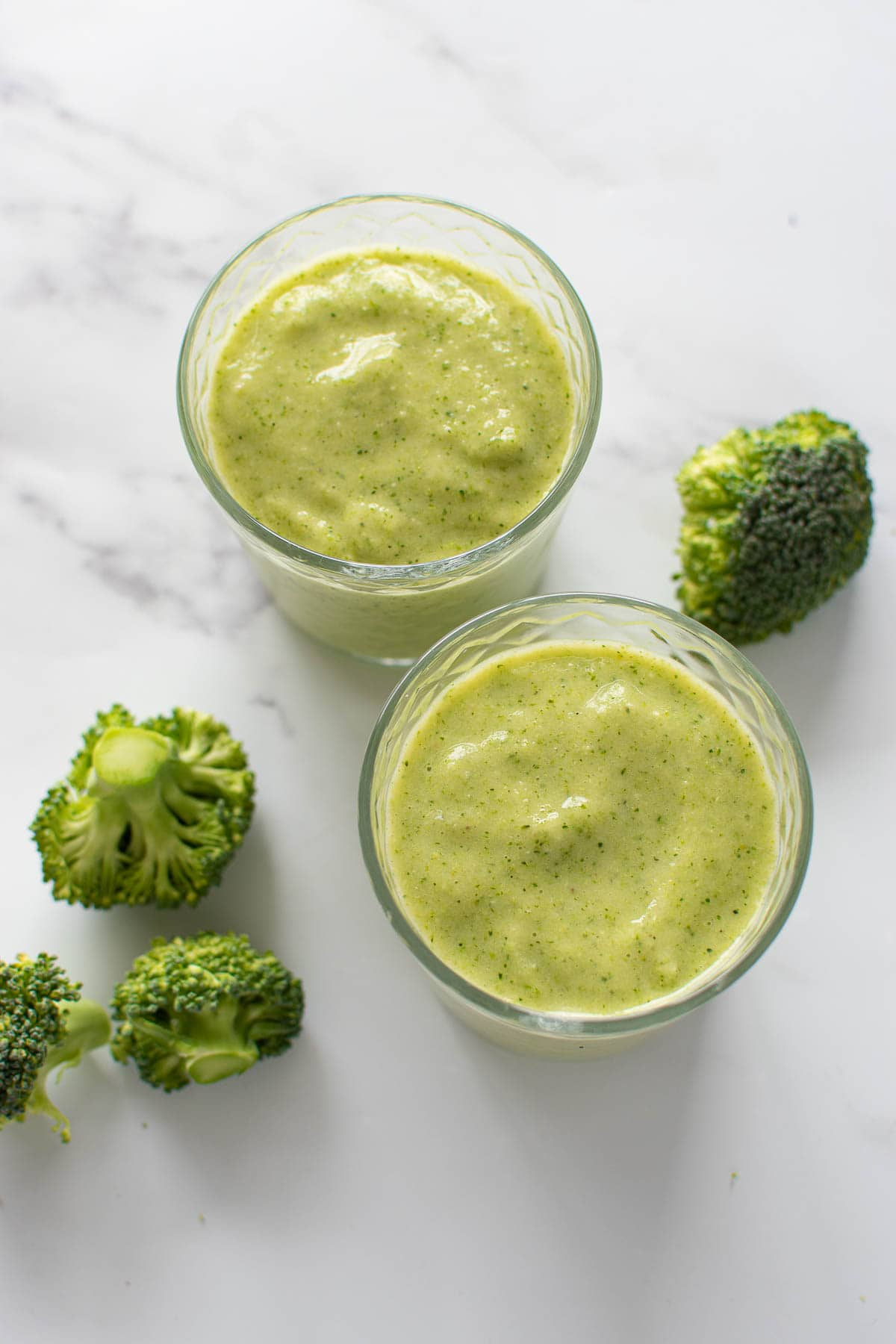 Glasses with pineapple and broccoli smoothie.