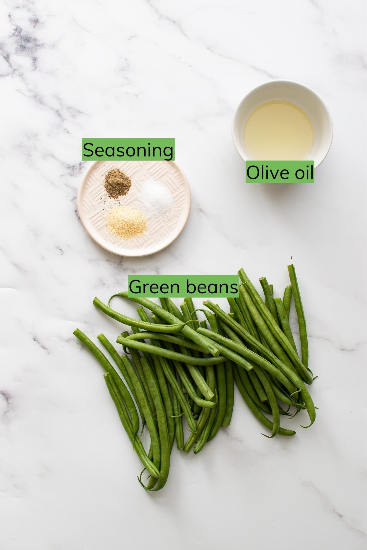 Green beans, seasoning and olive oil on a table.