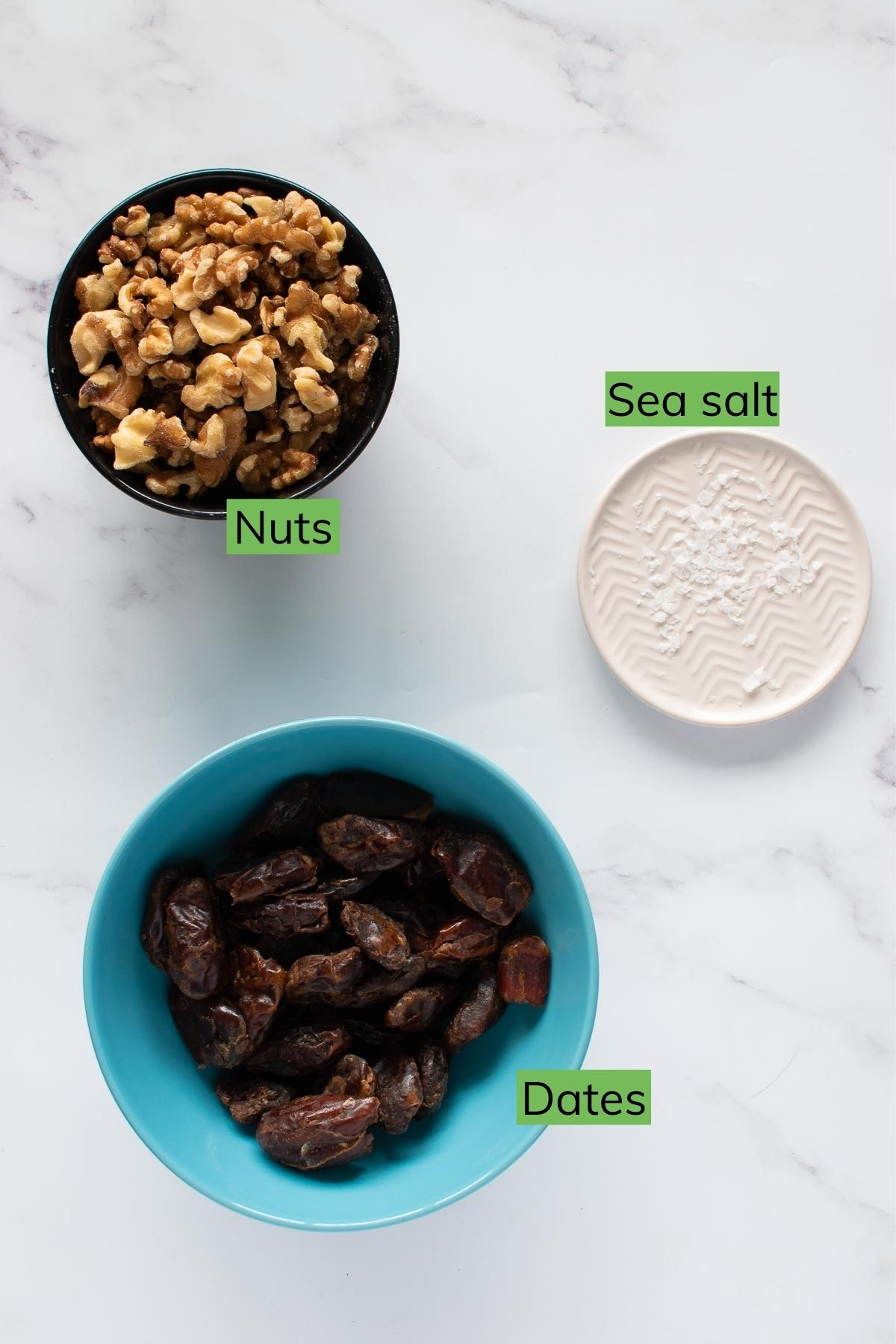 Nuts, dates and sea salt on a table.
