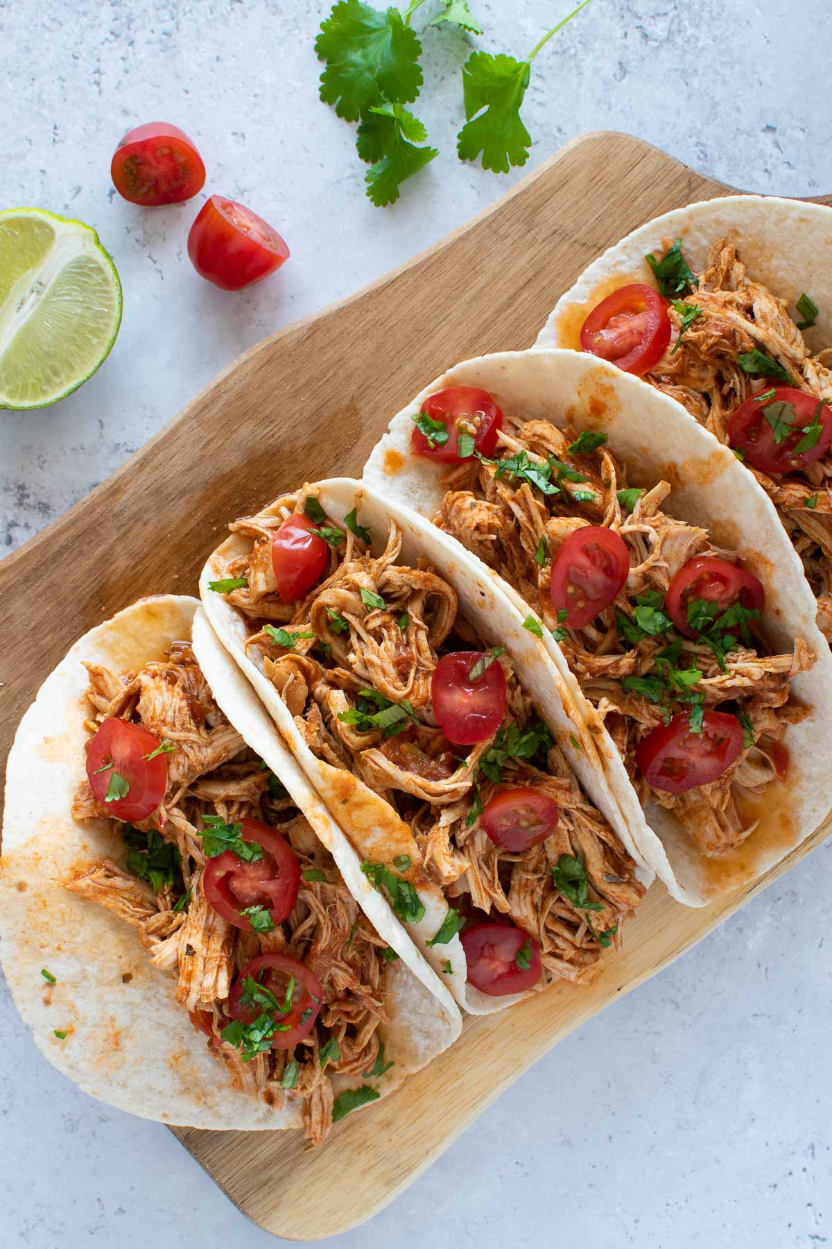 Instant Pot pulled chicken tacos on a cutting board.