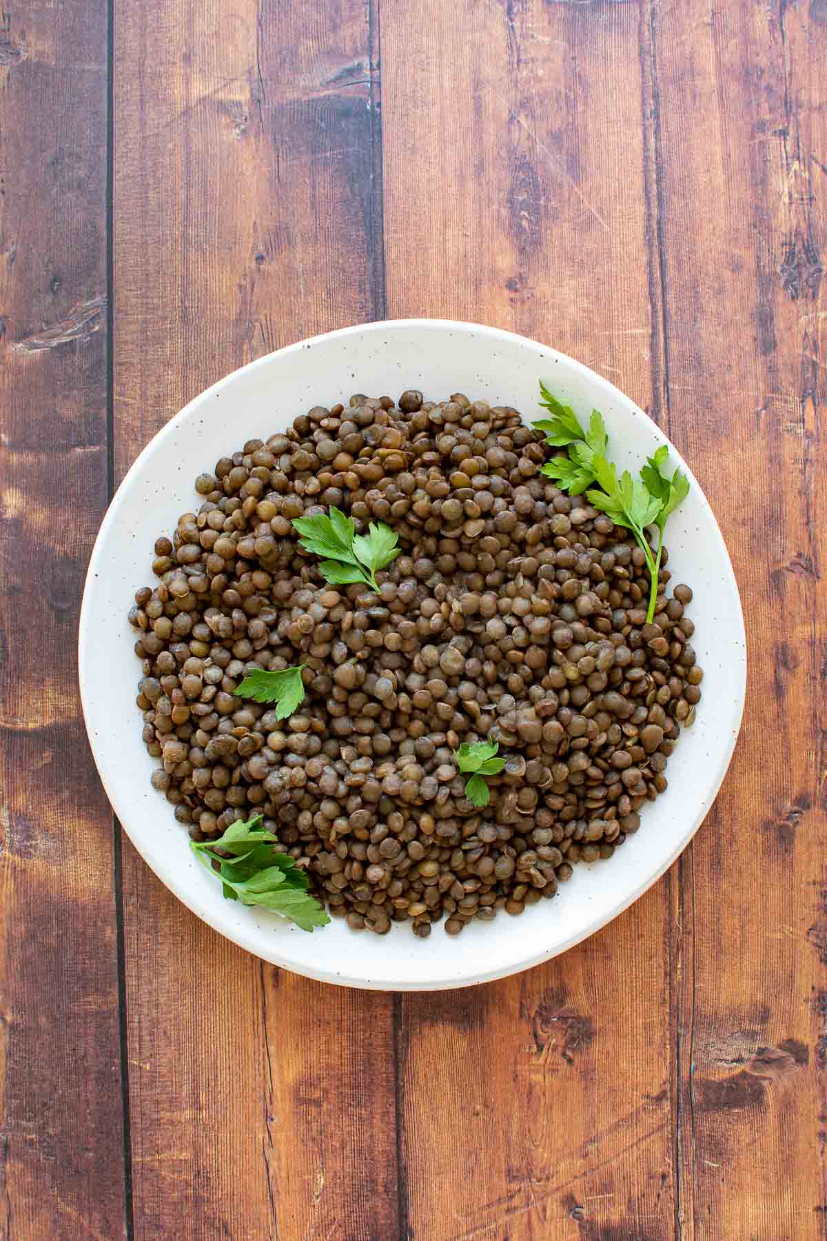 A plate of cooked lentils on a wooden table.