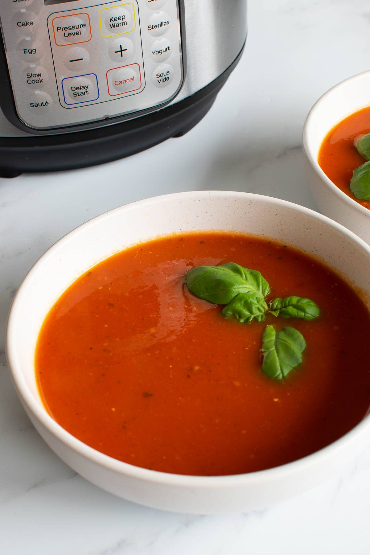 A bowl of tomato soup in front of an Instant Pot.