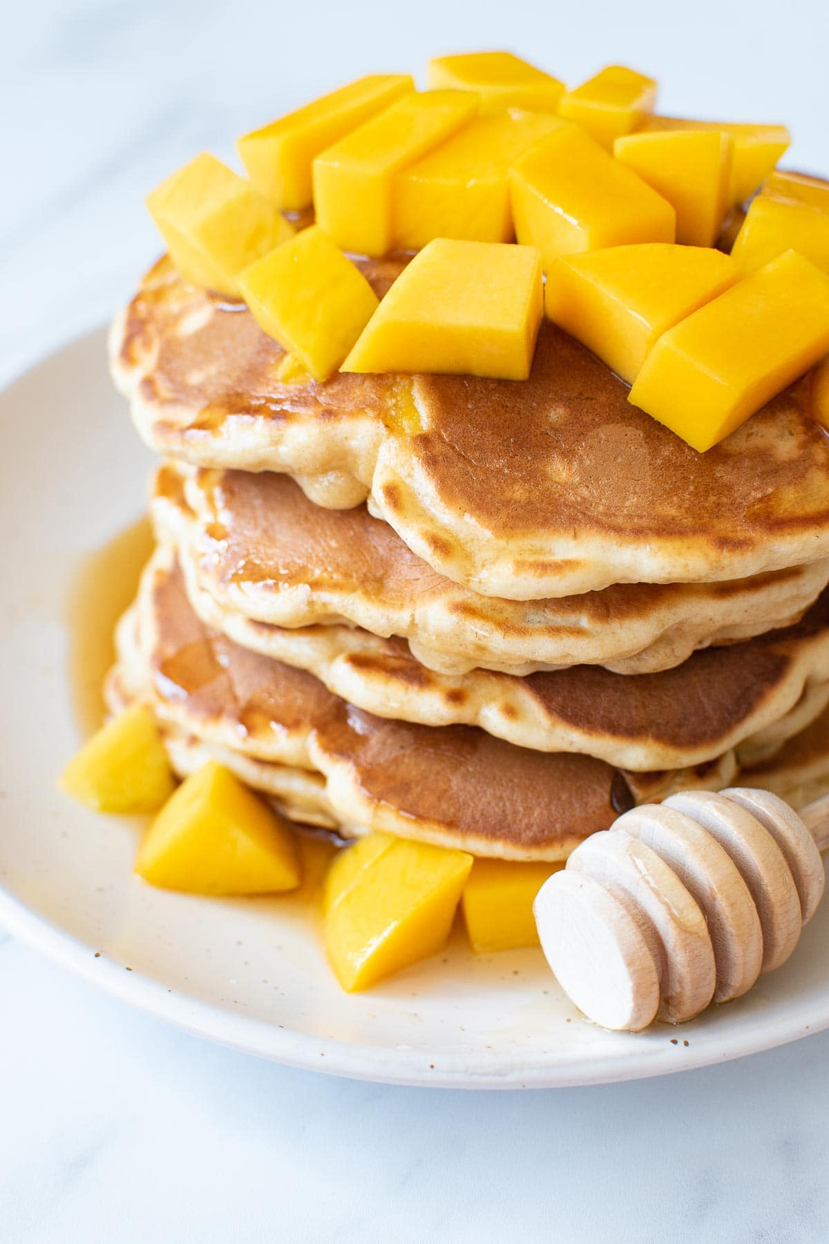 Close up of a stack of pancakes with mango.