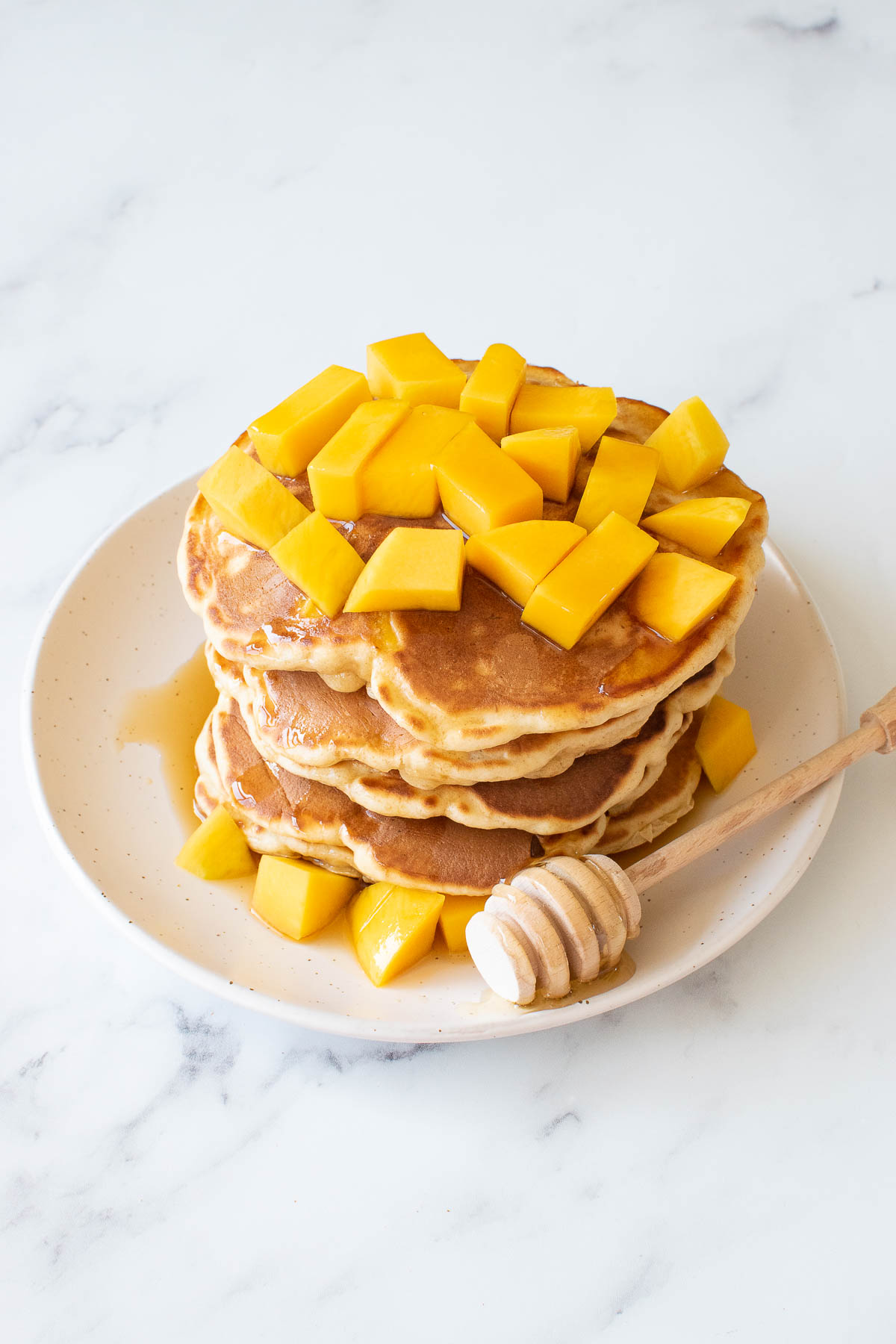 A stack of mango pancakes, with diced mango on top.