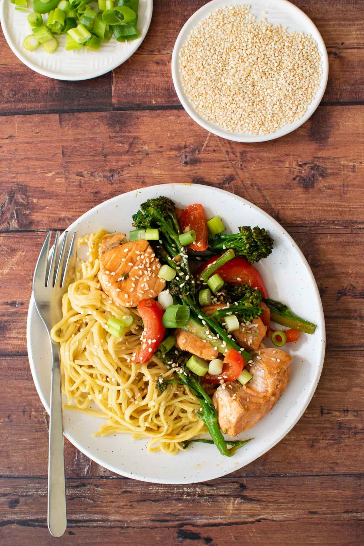 A plate with salmon and broccoli stir fry with noodles. Sesame seeds and scallions on the side.