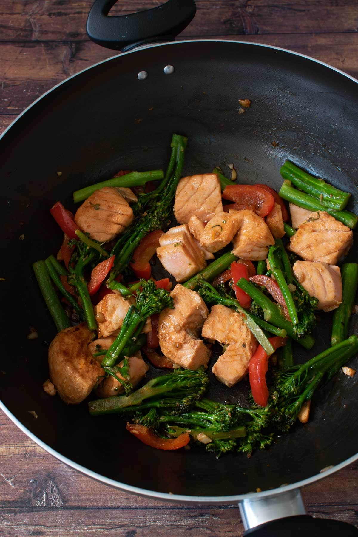 Salmon stir fry in a wok.