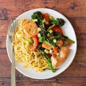 Salmon stir fry on a plate with noodles.