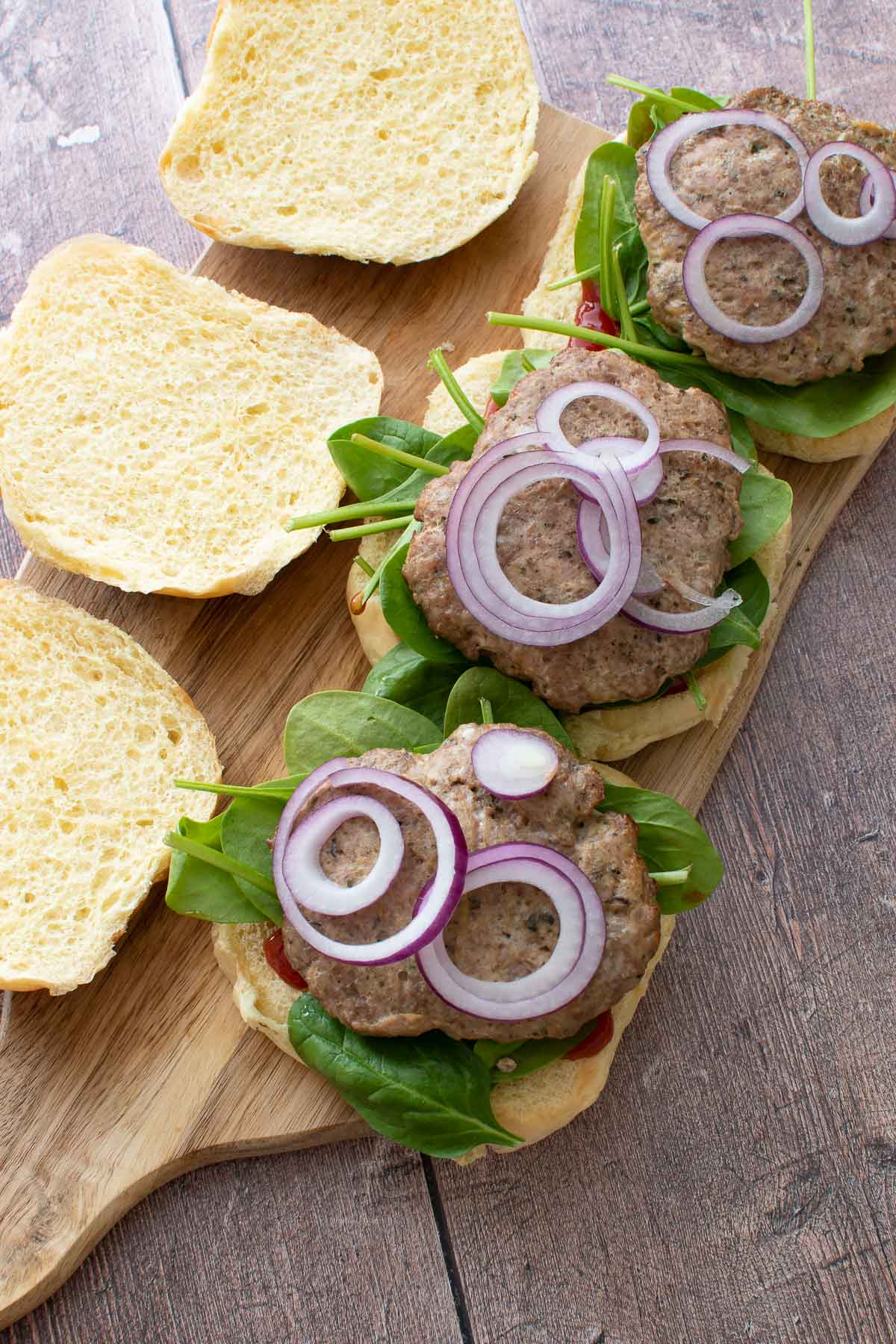 Baked ground turkey burgers with onion.